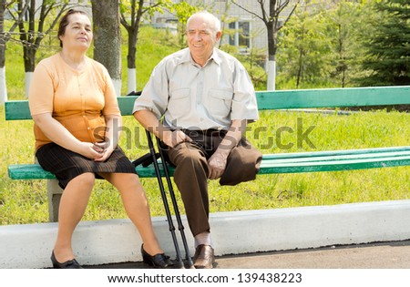 Portrait of couple talking and sitting on the park bench