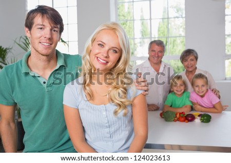 Portrait of couple with their family on background