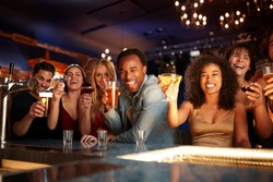 Portrait Of Couples With Friends Drinking In Bar Together