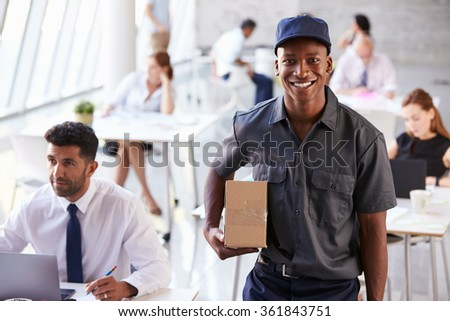 Portrait Of Courier Collecting Package From Busy Office