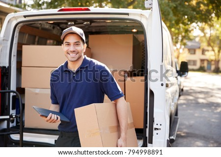 Portrait Of Courier With Digital Tablet Delivering Package