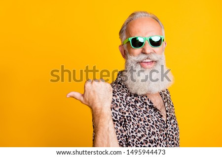 Portrait of crazy bearded old man point at copyspace reccomend promo ads feel funny funky wearing leopard shirt green eyeglasses eyewear isolated over yellow background