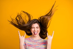 Portrait of crazy funky excited girl rock fan make horned symbol show tongue out close eyes enjoy rejoice her hairdo flying wear pullover isolated over bright shine yellow color background