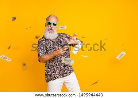 Portrait of crazy funny funky old long bearded man millionaire in eyewear eyeglasses waste money throw banknotes wear leopard shirt shorts isolated over yellow background
