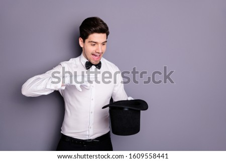 Portrait of crazy magician hold hand black cylinder hat make spell abracadbra entertain circus audience wear formalwear clothing isolated over grey color background