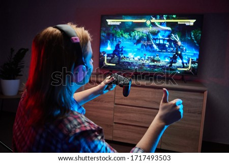 Portrait of crazy playful Gamer , girl enjoying Playing Video Games indoors sitting on the sofa, holding Console Gamepad in hands. Resting At Home, have a great Weekend Foto stock ©