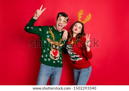 Portrait of crazy two family people wife husband brown hair lean shoulder make v-signs send air kiss lips pouted wear funny antler christmas tree clothes eyeglasses isolated over red color background