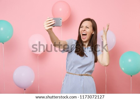 Portrait of crazy young woman in blue dress doing selfie on mobile phone screaming spreading hands on pastel pink background with colorful air balloons. Birthday holiday party people sincere emotions