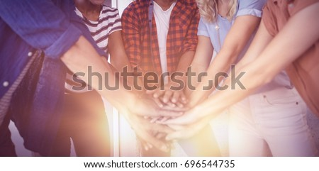 Portrait of creative business team stacking hands in office