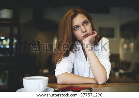 Portrait of creative  female manager of design company thinking over strategy for new project feeling upset waiting for inspiration and can't find original ideas spending leisure in coffee shop