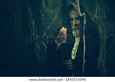 Portrait of creepy nun standing with a candle standing in the abandoned chapel. Horrors and Halloween.  Stock fotó ©