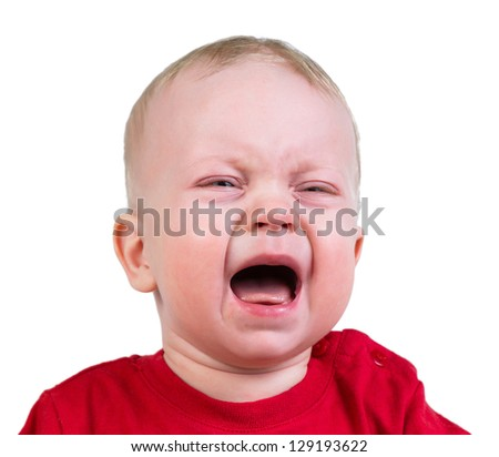 Portrait of crying 9-months old baby boy in red t-shirt, on white background.