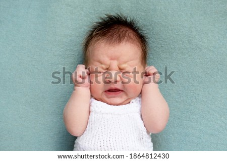 portrait of crying newborn baby. emotions of discontent. colic. Selective focus