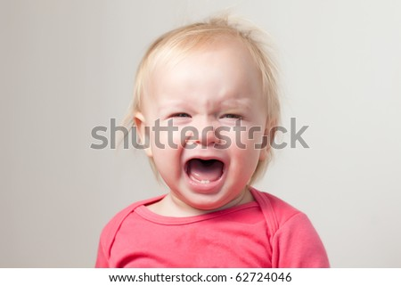 Portrait of crying young baby sit on chair