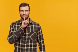 Portrait of cunning, adult male with brunette hair and beard. Wearing checkered shirt and accessories. Shows silence sign. Watching to the right at copy space, isolated over yellow background