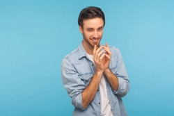 Portrait of cunning cheater, sneaky man in worker denim shirt gesticulating and thinking over devious sly plan of revenge, scheming and conspiring villain plan. studio shot isolated on blue background