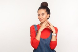 Portrait of cunning devious pretty girl with hair bun in denim overalls conspiring villain plan and smiling with sly tricky face, pondering revenge. indoor studio shot isolated on white background