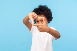 Portrait of curious nosy little boy in T-shirt looking through photo frame shape with fingers, focusing zooming at camera, viewing world with interest. indoor studio shot isolated on blue background