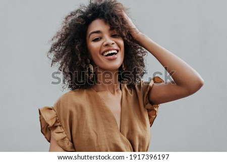 Portrait of curly brunette African dark-skinned woman in beige top smiling and ruffling hair on isolated grey background.