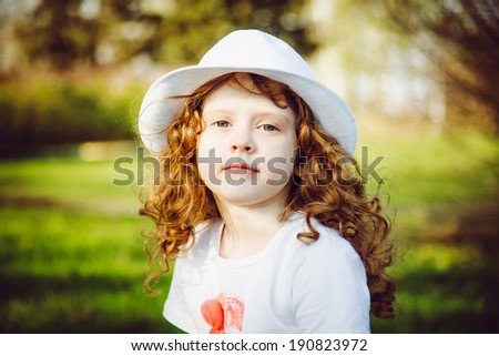 Portrait of curly girl in a white hat, toning in brown.