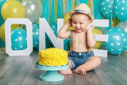 Portrait of cute adorable Caucasian baby boy wearing jeans pants and hat celebrating his first birthday. Cake smash concept. Child kid sitting on floor in studio eating tasty yellow dessert