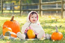 Portrait of cute adorable funny Asian Chinese baby girl sitting in autumn fall park outdoor with yellow orange pumpkins. Halloween or Thanksgiving seasonal concept. Autumnal harvest.