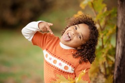 Portrait of cute adorable little  girl child making funny silly faces, showing tongue, in autumn fall park outside, playing having fun, lifestyle childhood