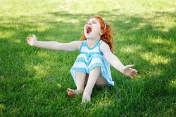 Portrait of cute adorable little red-haired Caucasian girl child in blue dress sitting on grass in park outside playing singing crying desperately, having fun, happy lifestyle childhood concept