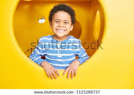 Portrait of cute African-American boy smiling happily peeking from round window of yellow cheese like box having fun on playground, copy space