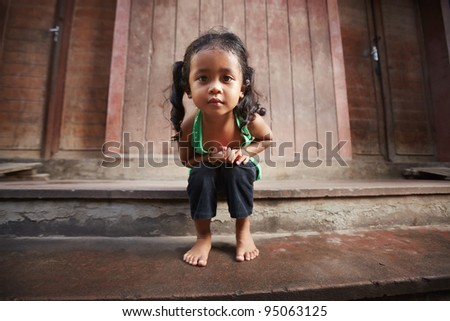 Portrait of cute Asian female child in green t-shirt sitting on street and looking at camera
