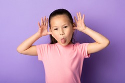 Portrait of cute asian kid sticking out her tongue and goofing at studio, isolated on pastel purple background