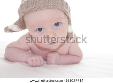 Portrait of cute baby boy in a knitted hat on white background
