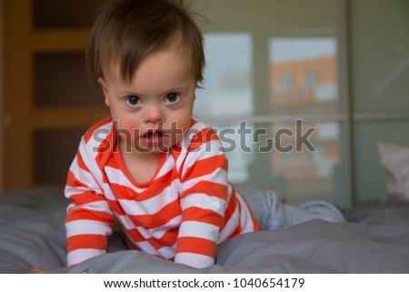 Portrait of cute baby boy with Down syndrome #1040654179
