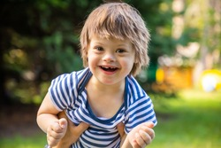 Portrait of Cute baby boy with Down syndrome playing in summer day on nature