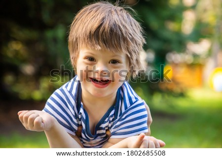 Portrait of Cute baby boy with Down syndrome playing in summer day on nature Stock photo ©