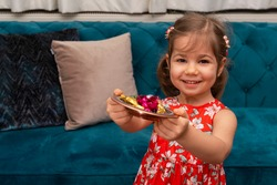 Portrait of cute baby girl holding candies from during Ramadan feast (aka: Ramazan or Seker bayrami). Sweets in little child hands as a tradition in middle eastern culture.