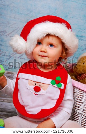 portrait of cute baby girl in red santa hat playing with toys