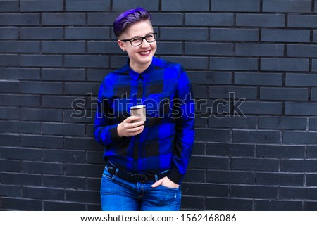 Portrait of cute beautiful young lesbian with short haircut and trendy boyish clothes drinking cup of coffee, friendly.  Stockfoto ©