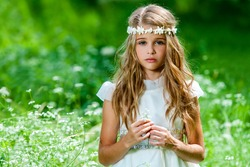 Portrait of cute blond girl dressed in white standing in green field.