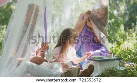 Portrait of cute blonde little girl with family in park