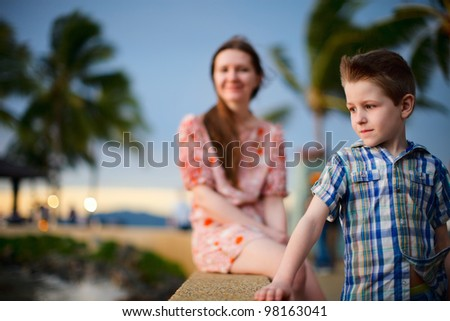 Portrait of cute boy and his mother enjoying sunset