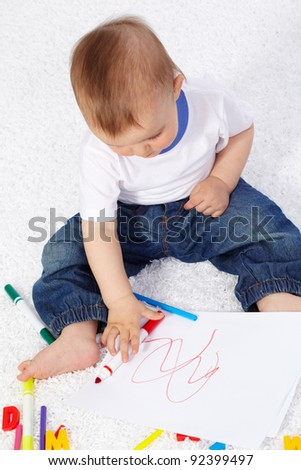 Portrait of cute boy drawing with crayons