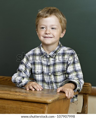 Portrait of cute boy front of a green blackboard.