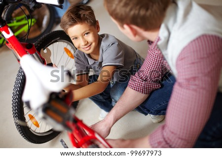 Portrait of cute boy looking at camera with his father repairing bicycle near by