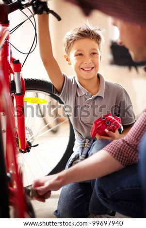 Portrait of cute boy looking at his father repairing bicycle in garage
