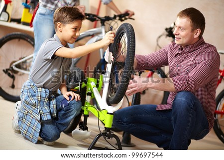 Portrait of cute boy repairing bicycle wheel with his father helping him near by
