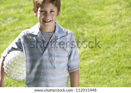 Portrait of cute boy standing with ball