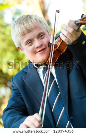 Portrait of cute boy with down syndrome playing violin outdoors.