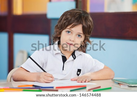 Portrait of cute boy with sketch pen and paper at desk in classroom