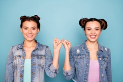 Portrait of cute charming satisfied hipsters person isolated holding hands together placing pinkies showing peace conciliation wearing modern denim clothing on pastel background